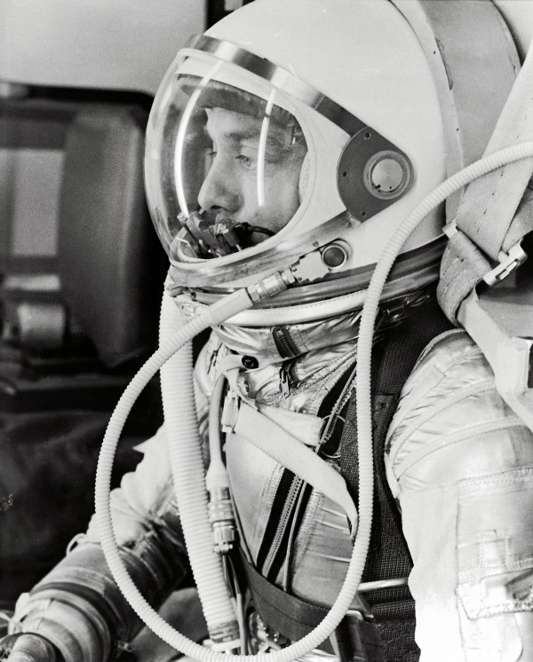 Young man's face seen through clear helmet visor, plastic pipes running from helmet to space suit.