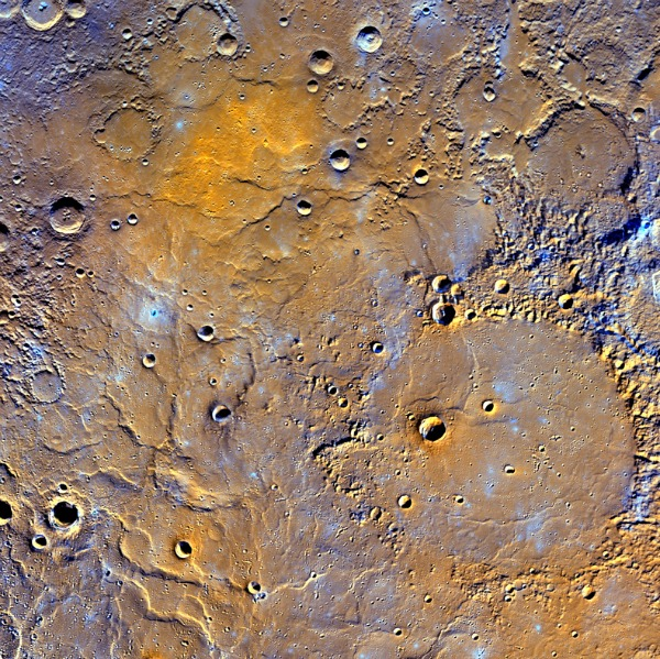 A view of Mercury's northern volcanic plains is shown in enhanced color to emphasize different types of rocks on Mercury's surface. In the bottom right portion of the image, the 181-mile- (291-kilometer)-diameter Mendelssohn impact basin, named after the German composer, appears to have been once nearly filled with lava. Toward the bottom left portion of the image, large wrinkle ridges, formed during lava cooling, are visible. Also in this region, the circular rims of impact craters buried by the lava can be identified. Near the top of the image, the bright orange region shows the location of a volcanic vent. Image credit: NASA/JHUAPL/Carnegie Institution of Washington