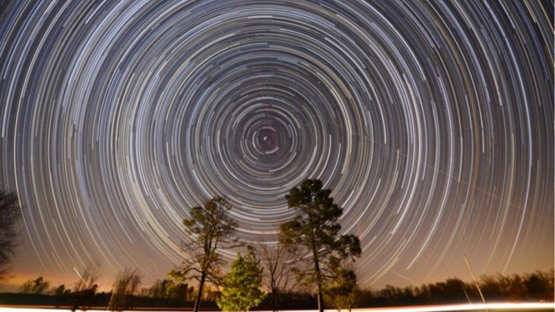 Many concentric white circles with one star in the center, over trees.