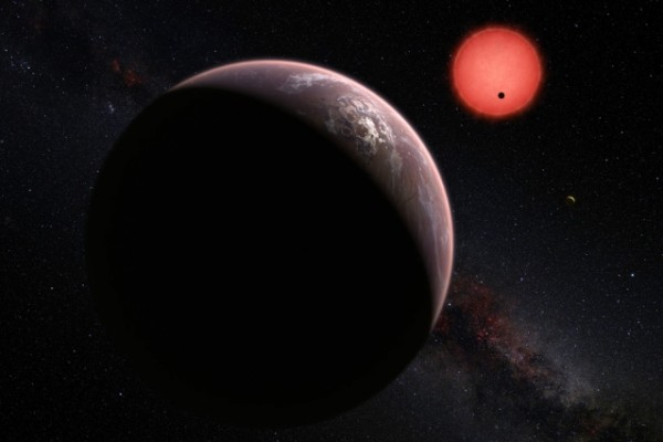 This artist's rendering shows an imagined view of the three planets orbiting an ultracool dwarf star just 40 light-years from Earth. In this view, one of the inner planets is seen in transit across the disc of its tiny and dim parent star. Image credit: M. Kornmesser/ESO