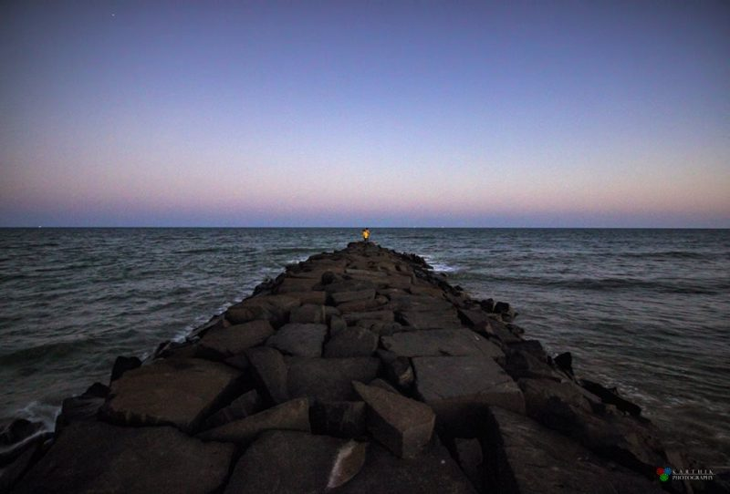 View straight along rocky breakwater with dot of light at end in dark twilight sky.