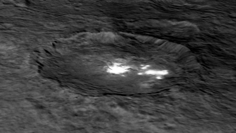 Oblique view of a crater on irregular terrain with very bright white patchs.
