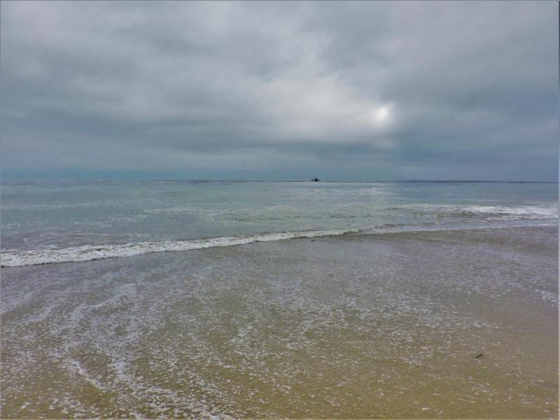 Edge of beach with wavelets under cloudy sky.