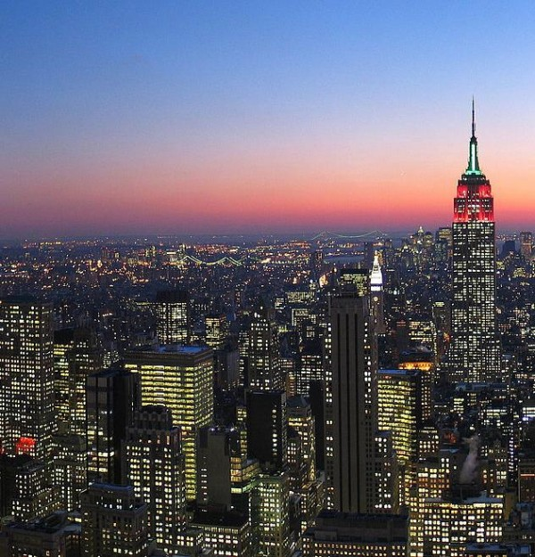 Twilight fading from deep blue to red over a cityscape glimmering with millions of lights, stretching to the horizon.