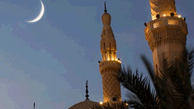 Crescent moon viewed beside minaret tower of a mosque against deep twilight sky.