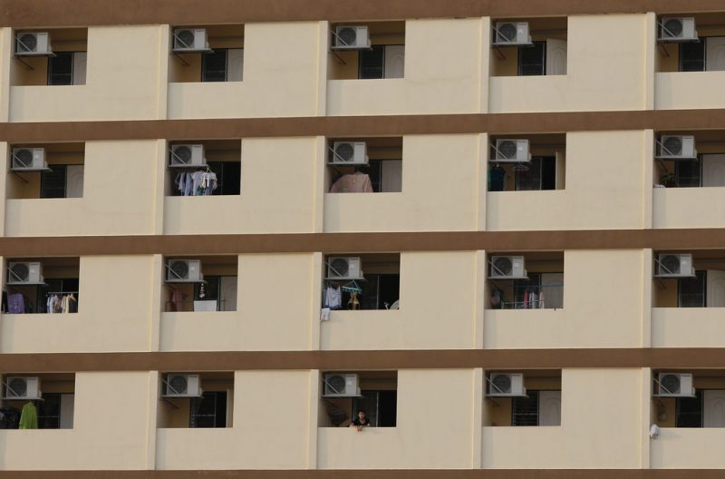 A housing complex in Thailand with air conditioners. Image via Chaiwat Subprasom/Reuters