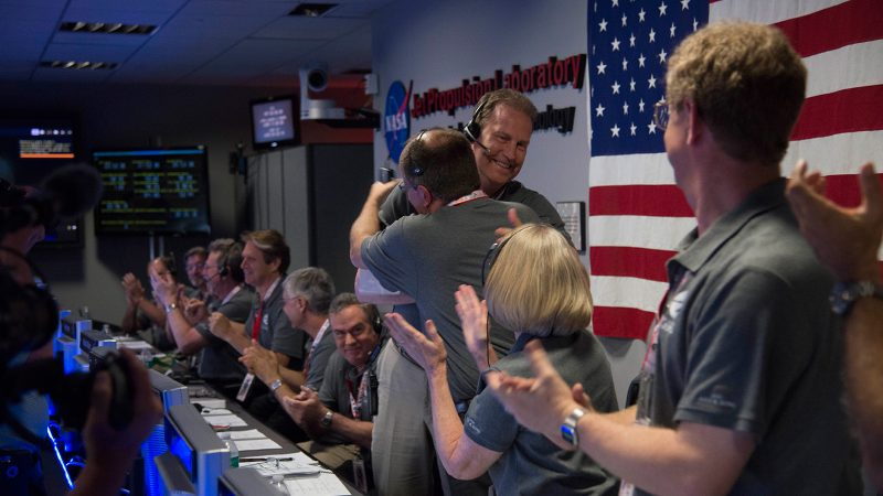 The Juno team celebrates at NASA's Jet Propulsion Laboratory in Pasadena, California, after receiving data indicating that NASA's Juno mission entered orbit around Jupiter. Rick Nybakken, Juno project manager at JPL, is seen at the center hugging JPL's acting director for solar system exploration, Richard Cook. Image Credit: NASA/JPL-Caltech