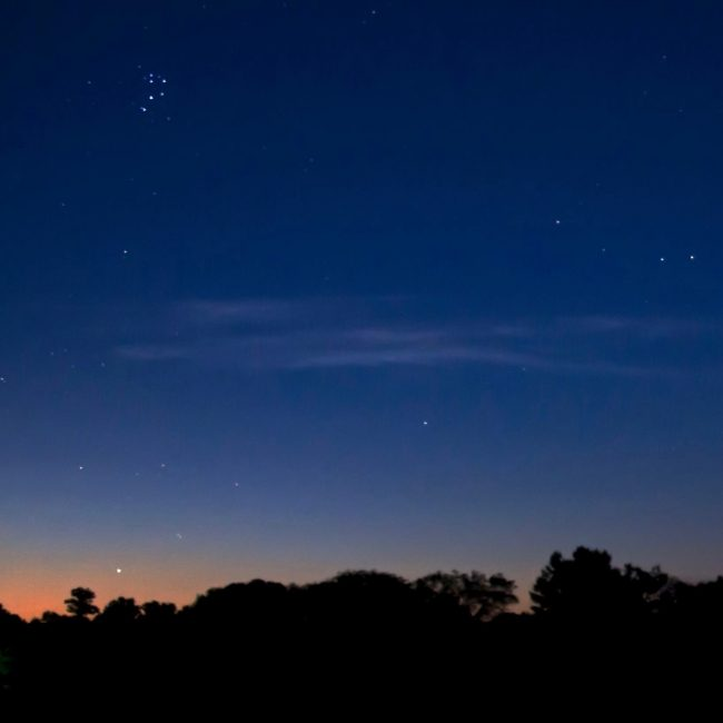 See the star Aldebaran just above the twilight in this photo by Ken Christison?  Notice that it's part of a V-shaped pattern of stars. Look above Aldebaran.  See the Pleiades?
