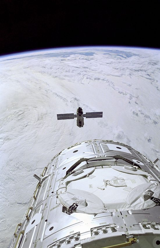 Backdropped against a blanket of heavy cloud cover, the Russian-built FGB, also called Zarya, nears the Space Shuttle Endeavour and the U.S.-built Node 1, also called Unity (foreground). Inside Endeavour's cabin, the STS-88 crew readies the Remote Manipulator System (RMS) for Zarya capture as they await the carefully choreographed dance of the rendezvous. Image via Wikimedia Commons.