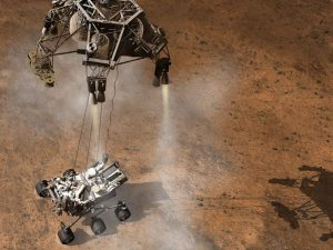 A spacecraft hovering above Mars' surface, firing retrorockets, with cables from the craft lowering the rover to the surface of Mars.