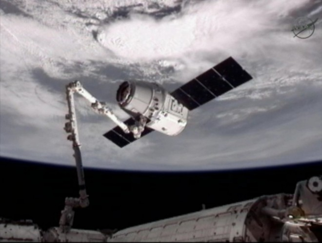 "astronaut Don Pettit control the station's robotic arm and grapple the Dragon at 6:56 a.m. PDT. ""Looks like we've got a Dragon by the tail,"" Pettit said from the station's Cupola module once the capture was made. NASA photo via Wired."