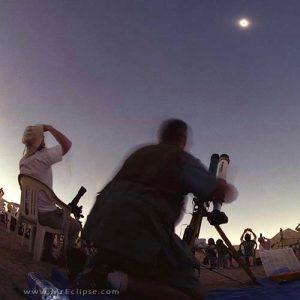 Silhouette of man at telescope, gazing toward an eclipsed sun.