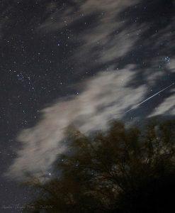 Long bright diagonal line streaking among clouds.