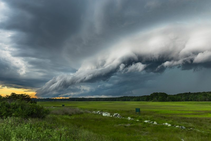 Odd-looking shelf cloud above a field.