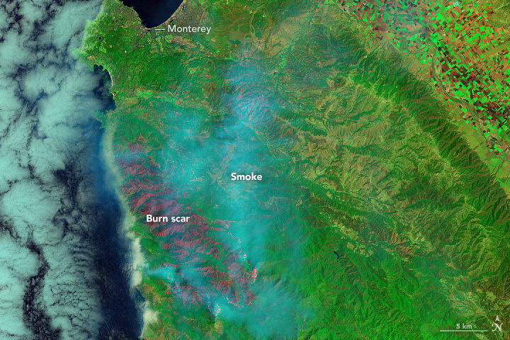 July 29, 2016. In this false-color view, active fires are bright red and orange, scarred land is dark red, and intact vegetation and human development are green.  Image via NASA.
