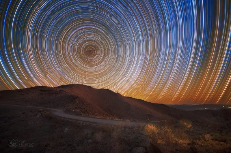 Concentric circles of light over a mountainous landscape.