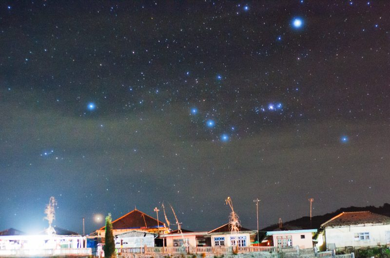 Constellation Orion with stars very bright in a slightly cloudy sky, rising behind a village.