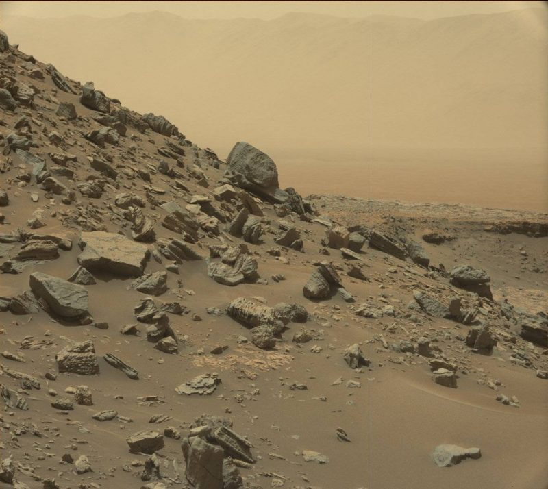 The rim of Gale Crater is visible in the distance, through the dusty haze, in this Curiosity view of a sloping hillside on Mount Sharp. Image via NASA/JPL-Caltech/MSSS