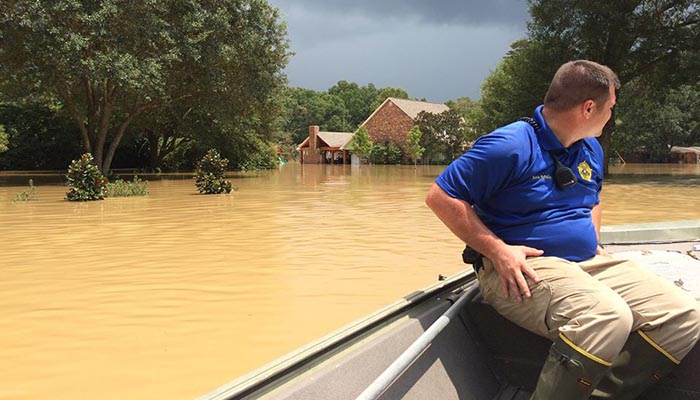 A Livingston Parish deputy sheriff surveys flood damage from a boat on August 15, 2016.  Image courtesy of Rapides County Sheriff's Office