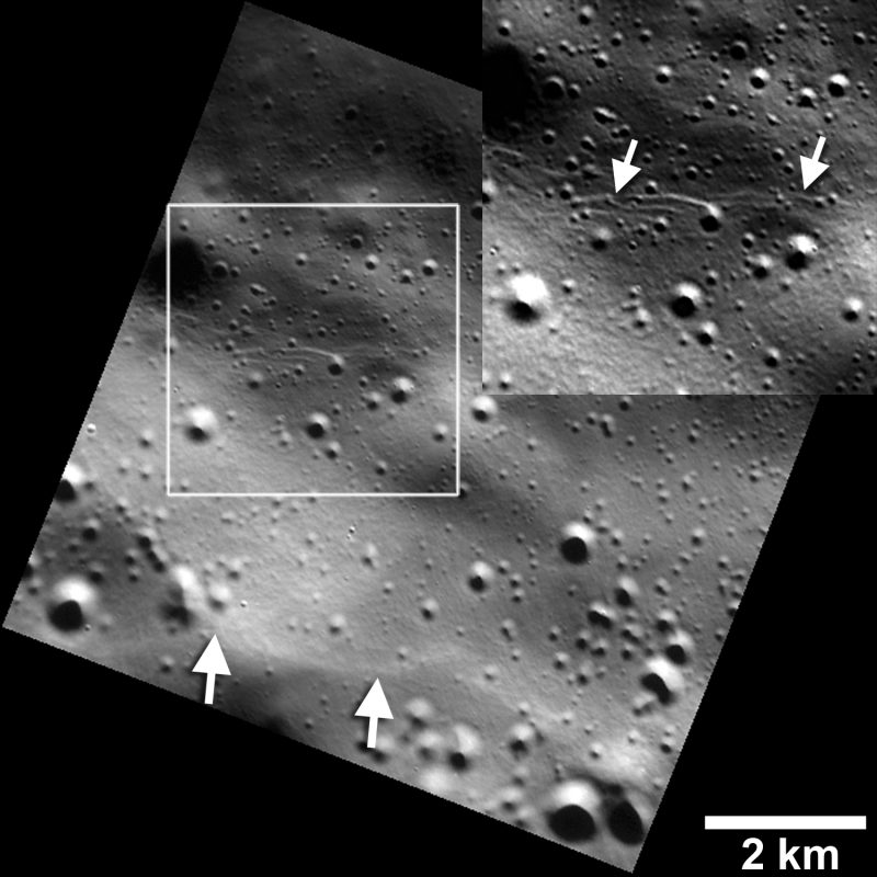 Small graben, or narrow linear troughs, have been found associated with small fault scarps (lower white arrows) on Mercury, and on Earth's moon. The small troughs, only tens of meters wide (inset box and upper white arrows), likely resulted from the bending of the crust as it was uplifted, and must be very young to survive continuous meteoroid bombardment. Image via NASA/JHUAPL/Carnegie Institution of Washington/Smithsonian Institution