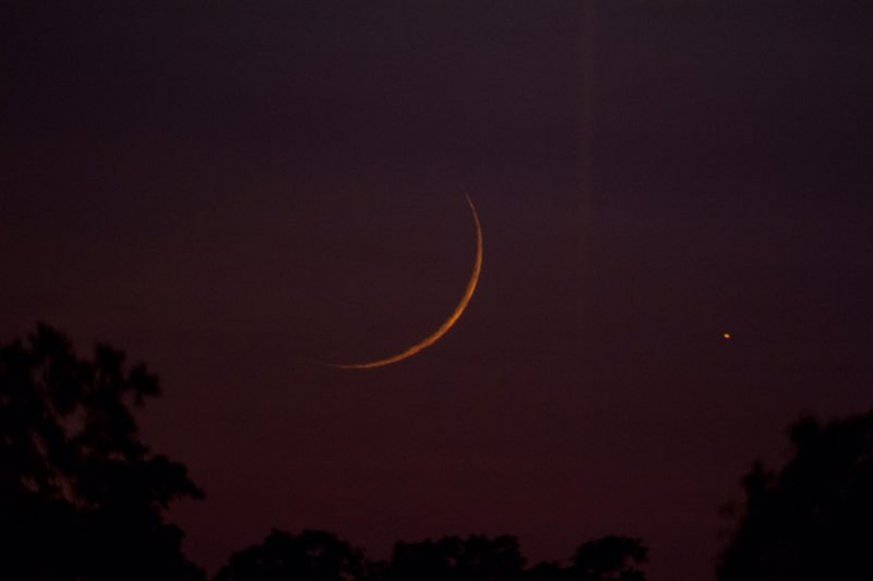 Very thin orange crescent in deep reddish purple sky with a bright dot to its right.
