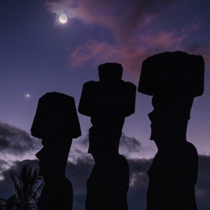 Three tall stone figures with human profiles and large cylindrical hats silhouetted against a cloudy twilight sky.