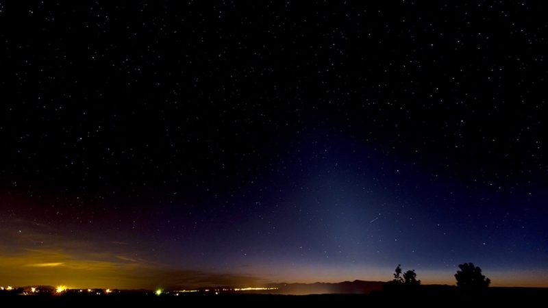 The zodiacal light is a diffuse cone-shaped light extending up from the horizon on the right side of this photo. Photo by Richard Hasbrouck in Truchas, New Mexico.