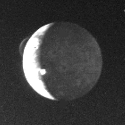 Discovery image of active volcanism on Io. The plumes of Pele and Loki are visible above the limb and at the terminator, respectively. Image via NASA PhotoJournal.