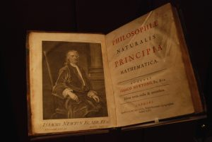 Small book, open, with portrait of Newton on left page and title in red and black on right page.