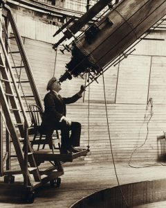 Man in early 20th century clothing, sitting at the eyepiece of a large telescope.