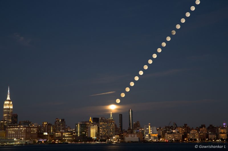 This composite image captures the Hunter moon rise over the Manhattan skyline taken across the Hudson river from the Hoboken Pier C park waterfront. This image consists of 19 images stacked into one.