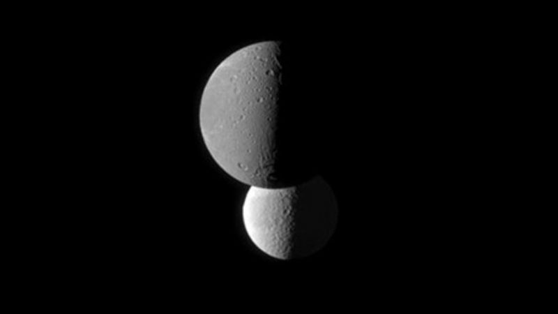 Saturn's moon Dione, foreground, appears darker than the moon Tethys because it has a lower surface albedo, as shown in a photograph taken from the Cassini spacecraft on March 23, 2010. At the time, Cassini was about 746,000 miles from Dione and about 1.1 million miles from Tethys. Image via NASA JPL.