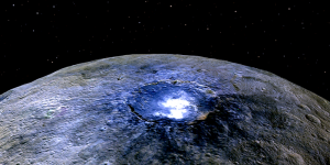 Surface of a round, rocky body with a large crater with bright white spots in it.