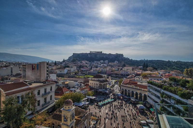 City below a citadel with columns of ruinous Parthenon visible at top.
