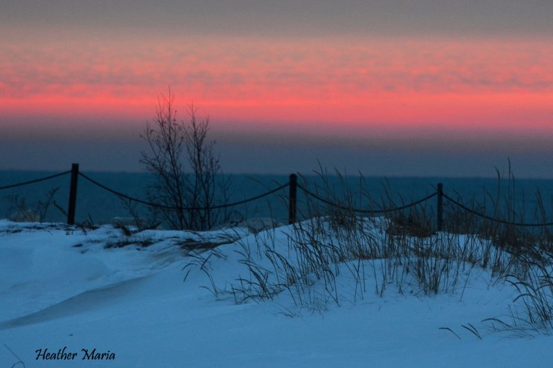 Snow on dunes in foreground, ocean, pink strip of sunrise.