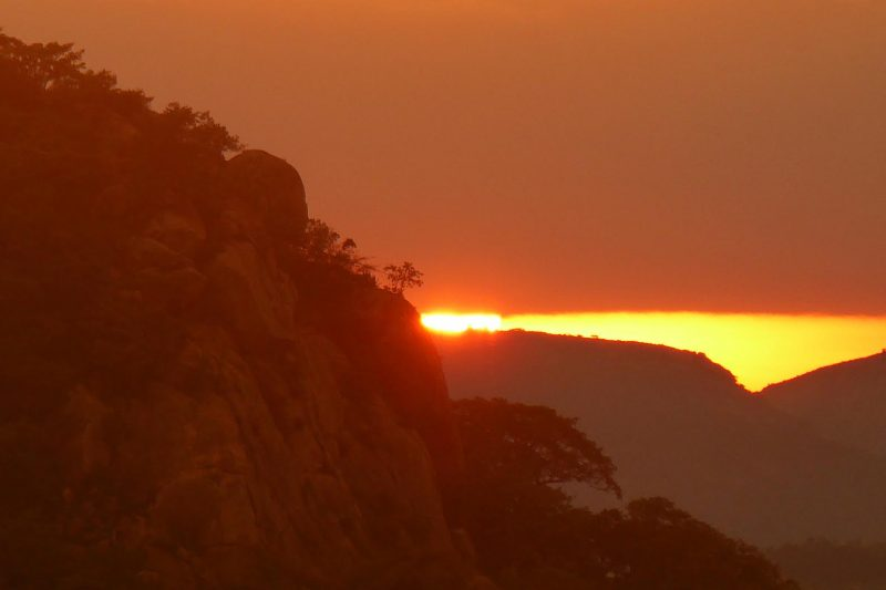Sun just visible over horizon of hillside.