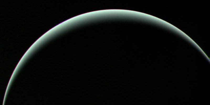 A crescent image of Uranus blue-green against a black sky.
