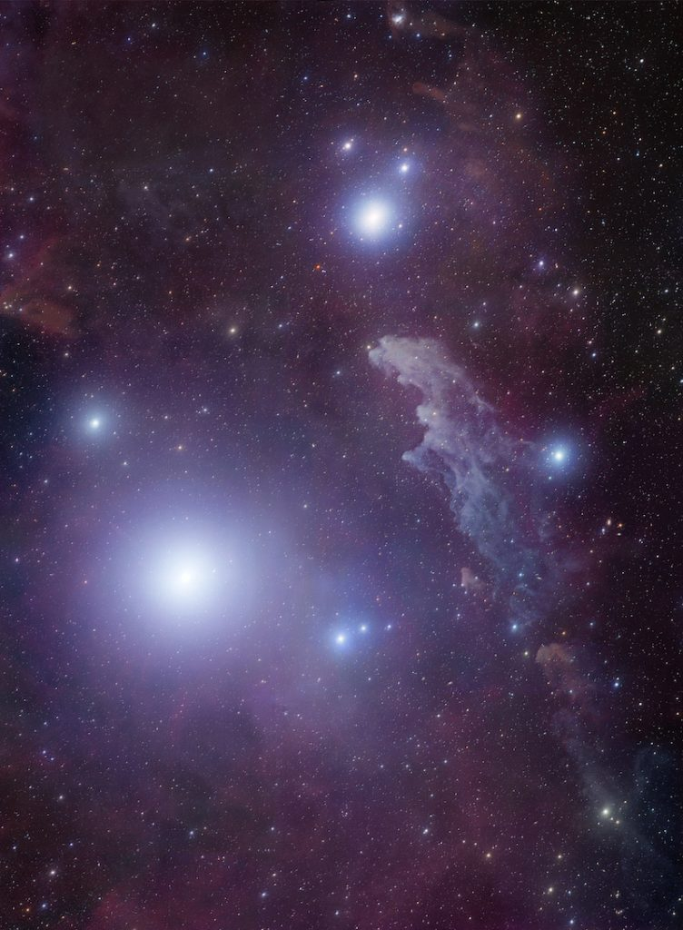 Seveal bright stars with blue halos near elongated, lumpy pale blue cloud against star field.