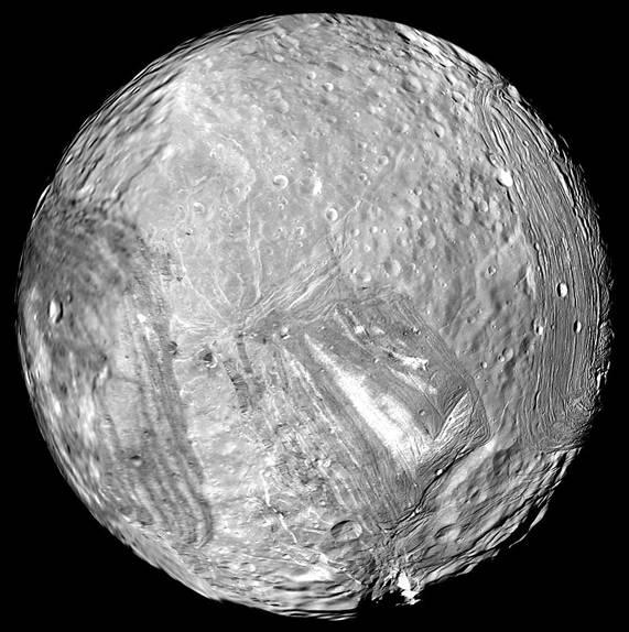 Round gray moon with craters, lines, streaks and white patches.