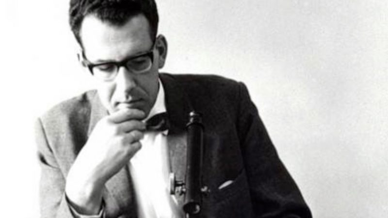 Portrait of man wearing glasses, hand on chin, looking thoughtful.