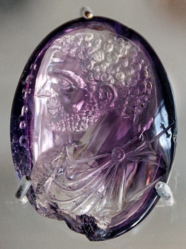 Man's head with curly hair and beard carved in low relief on an oval purple stone.