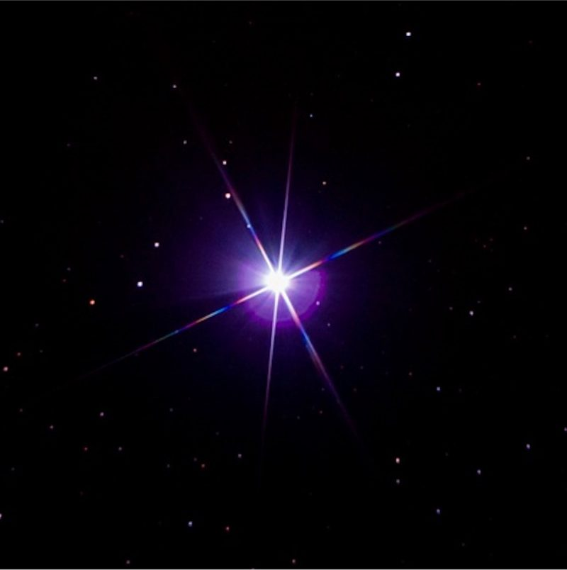 Enlarged star with six rays striped with colors.