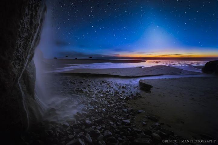Rocky landscape, dawn light on horizon, zodiacal light extending upward.