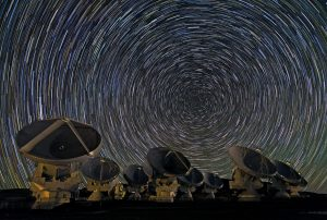 Very, very many short white concentric lines in the sky above 8 large radio telescope dishes.