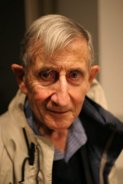 Old man with swooping gray hair in a jacket.