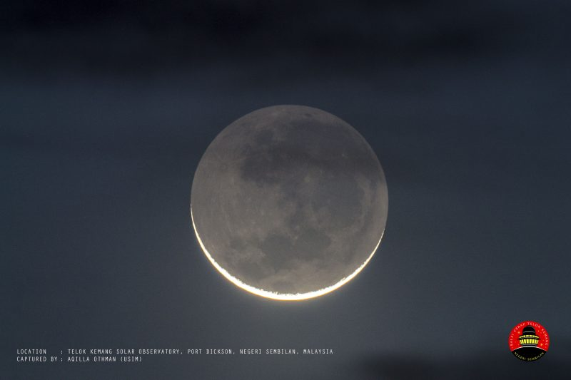 Bright narrow crescent moon with rest of moon showing pale gray.
