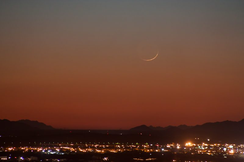 thin crescent moon over lights of a city with mountains on the horizon