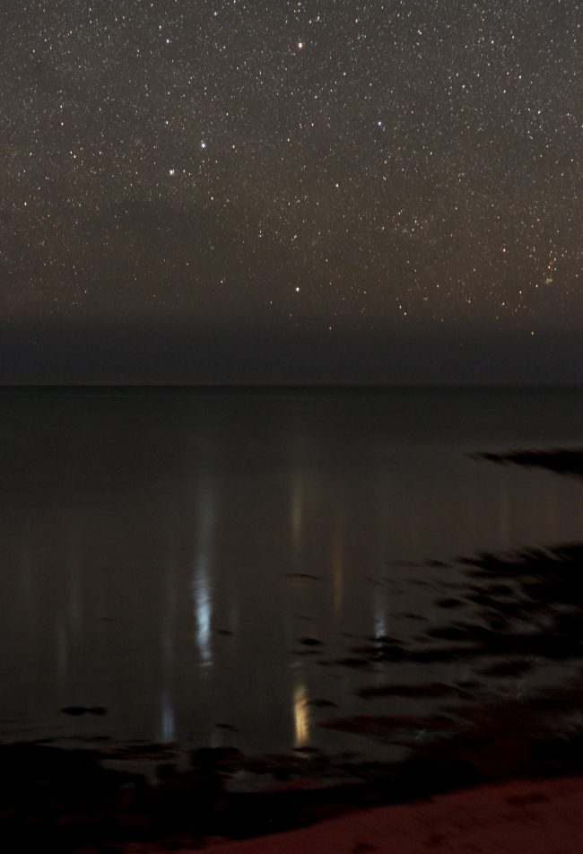 Star field over reflective body of water.
