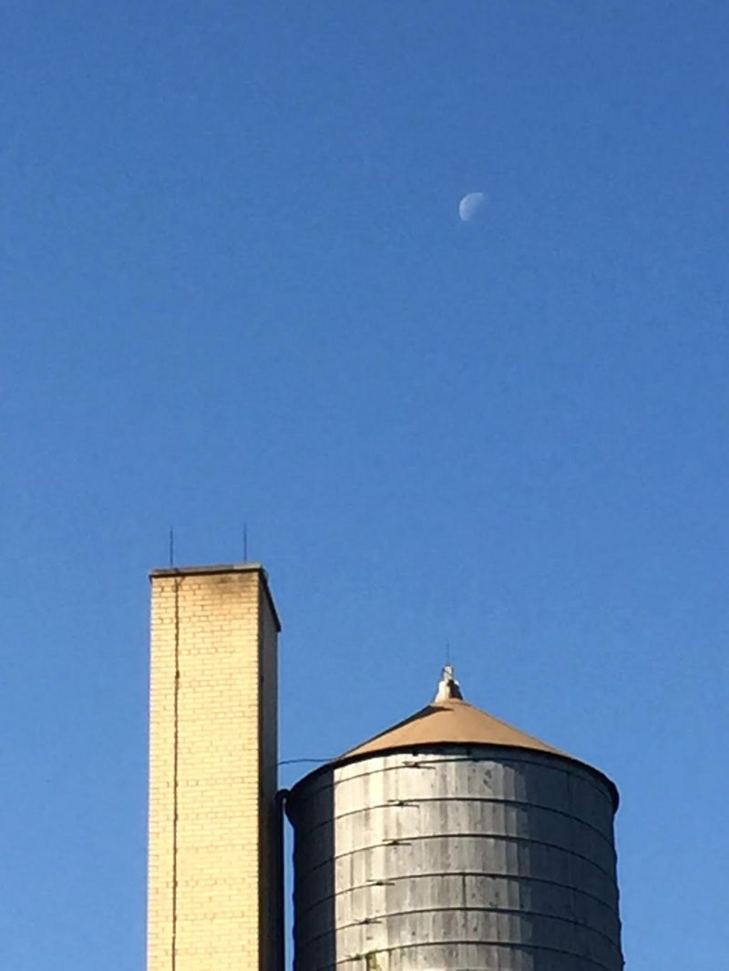 Daytime sky. High small moon, left half visible, above conical-top water tower and tall tan brick chimney.