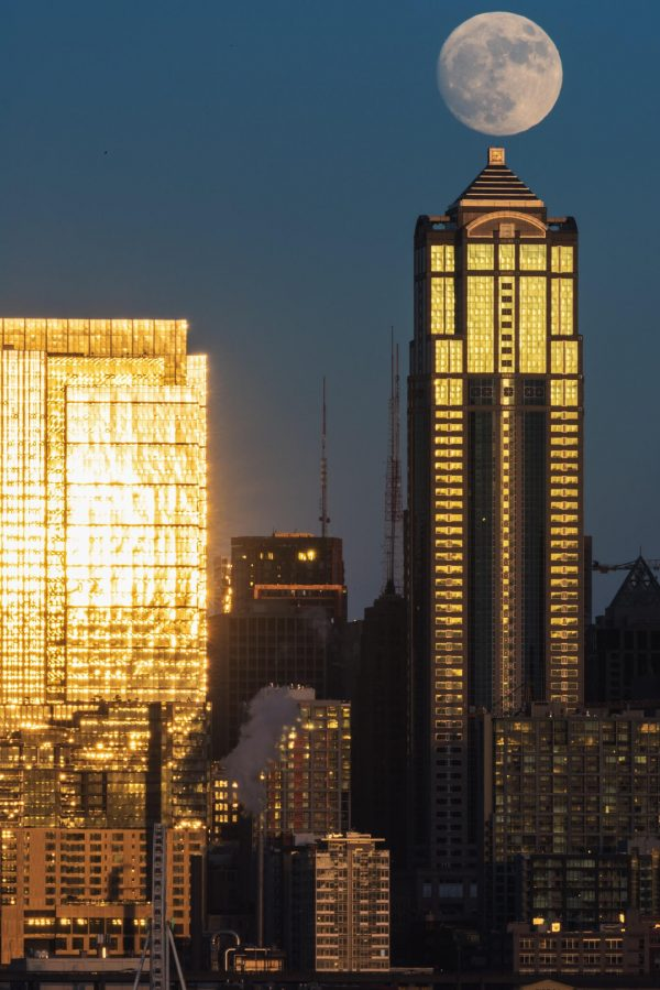 Full moon poised at top point of tall, shiny glass tower, another all glass building to the side.